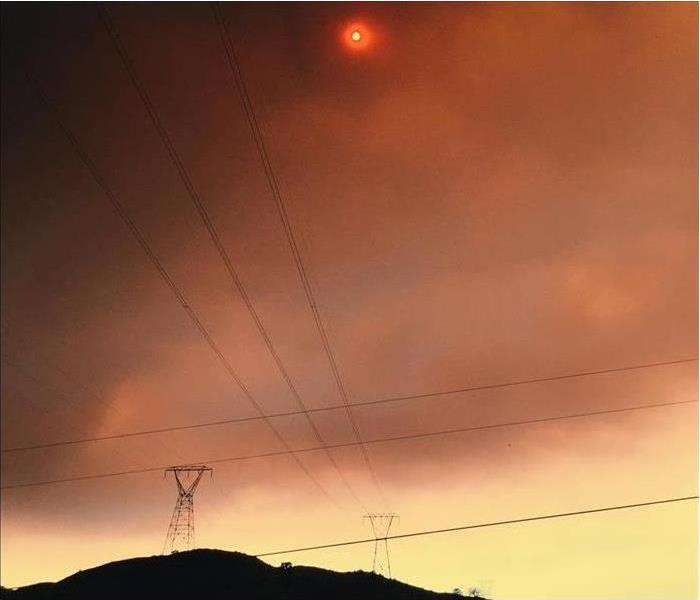 A smokey and orange sky with a telephone pole