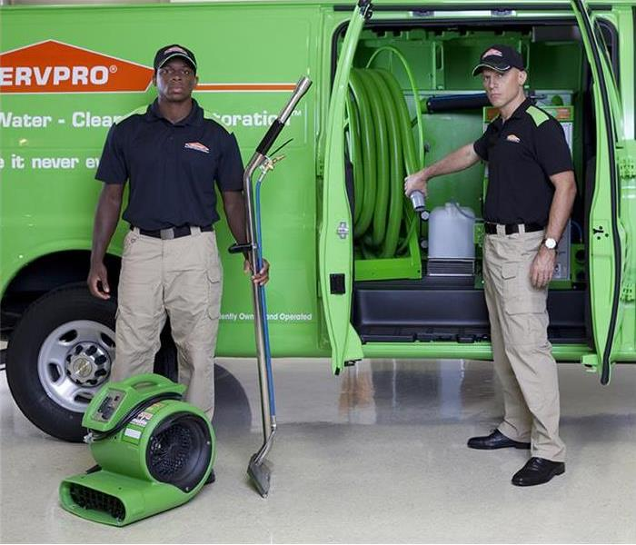 Two crew members by a SERVPRO van